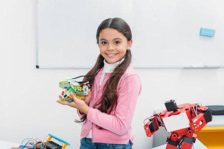 smiling schoolgirl looking at camera and presenting handmade robot model at STEM lesson