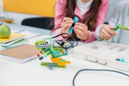 Photo pour Vue recadrée de camarades de classe travaillant ensemble sur le projet pendant la leçon de STIM avec modèle de robot fait à la main au premier plan - image libre de droit