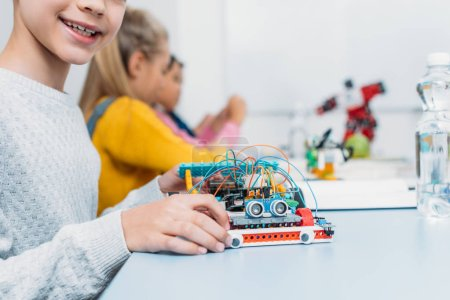 Foto de Recortar vista de colegial con modelo de robot hecha a mano y compañeros de clase trabajan juntos en proyecto durante la lección de la madre en el fondo - Imagen libre de derechos