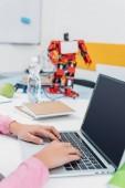 """Постер, картина, фотообои """"обрезанный вид школьница сидит за столом с робот модели и с помощью ноутбука с пустой экран во время урока стволовых"""""""