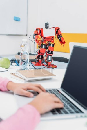 cropped view of schoolgirl sitting at table with robot model and using laptop with blank screen during STEM lesson