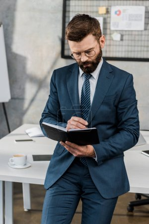 focused bearded businessman writing in notebook in office