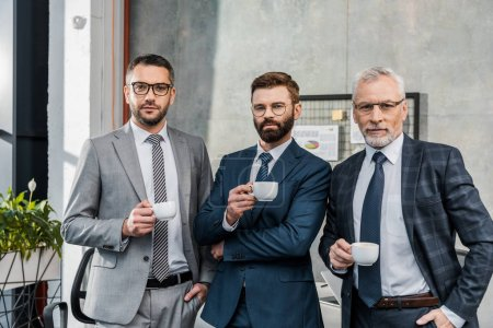 three confident businessmen holding cups of coffee and looking at camera in office