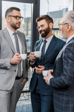 three smiling businessmen in formal wear drinking coffee and talking in office