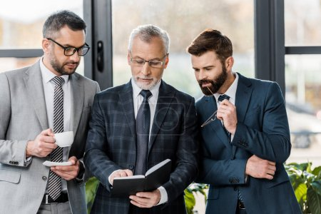 professional businessmen in formal wear standing together and looking at notepad