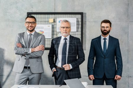 three confident professional businessmen standing together and looking at camera in office