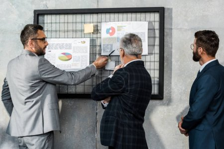 Photo for Back view of businessmen in formal wear looking at charts on wall - Royalty Free Image