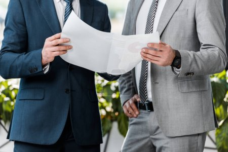 cropped shot of businessmen holding paper with charts and working together in office