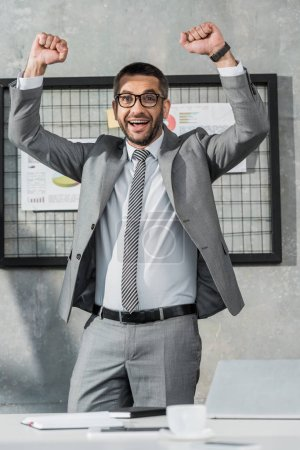 cheerful businessman triumphing and smiling at camera in office
