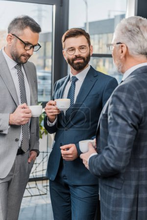 businessmen holding cups of coffee and talking in office