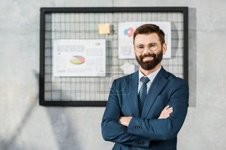 handsome confident bearded businessman standing with crossed arms and smiling at camera in office
