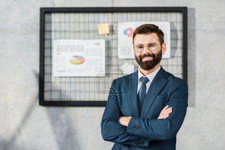 Foto de Apuesto seguro barbudo hombre de negocios de pie con los brazos cruzados y sonriendo a la cámara en la oficina - Imagen libre de derechos