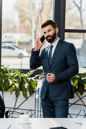 Photo for Smiling bearded businessman in formal wear talking by smartphone in office - Royalty Free Image
