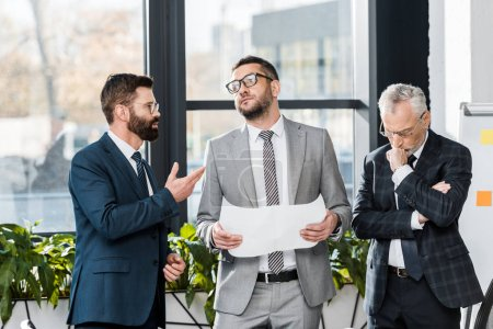 Photo for Serious professional businessmen discussing blueprint while standing in office - Royalty Free Image