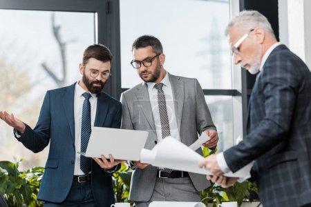 Photo pour Trois entrepreneurs professionnels sérieux travaillant avec les papiers et ordinateur portable au bureau - image libre de droit