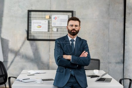 confident bearded businessman standing with crossed arms and looking at camera in office