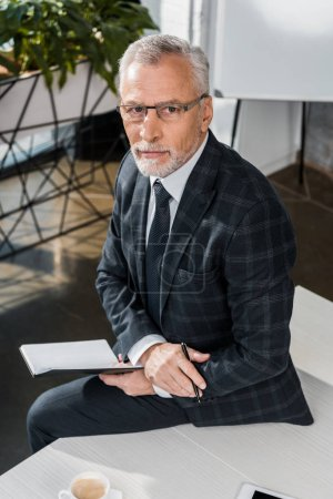 Photo for High angle view of serious mature businessman sitting on office table and looking at camera - Royalty Free Image