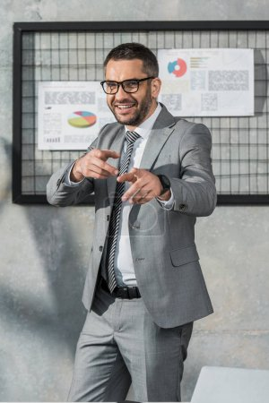 cheerful businessman in suit and eyeglasses pointing with fingers and smiling at camera in office