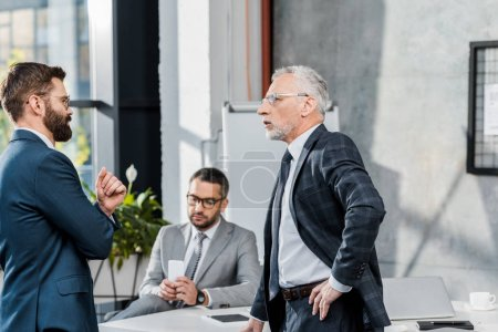 Photo for Side view of businessmen talking while standing in office - Royalty Free Image