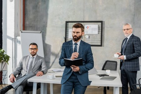 three professional businessmen in formal wear working together in office