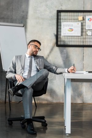 Photo for Bored businessman sitting at workplace and holding pen - Royalty Free Image