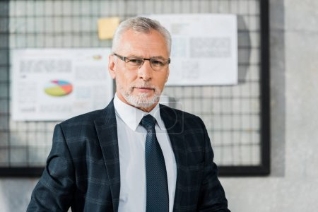 Photo for Portrait of handsome mature businessman in suit and eyeglasses looking at camera in office - Royalty Free Image