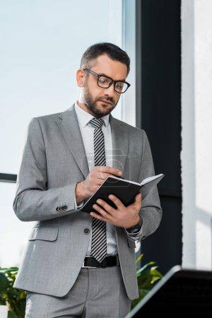 Photo pour Bel homme barbu en costume et lunettes permanent et écrire dans le cahier au lieu de travail - image libre de droit