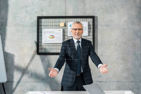 cheerful mature businessman standing with open arms and smiling at camera in office