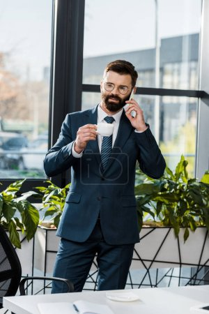 bearded buisnessman in suit and eyeglasses holding cup of coffee and talking by smartphone in office