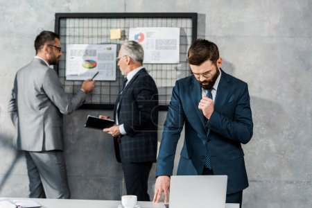 Photo for Bearded businessman using laptop and looking down while colleagues working with business charts behind - Royalty Free Image