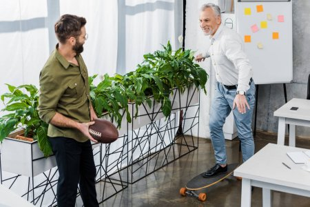 smiling businessmen having fun with skateboard and rugby ball in office