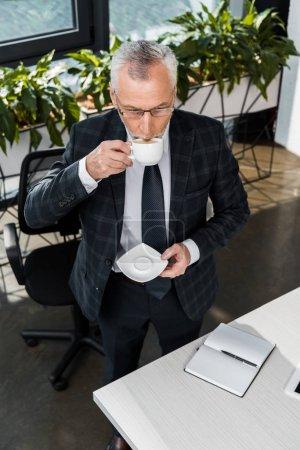 Foto de Vista de ángulo alto de maduro empresario tomando café en la oficina - Imagen libre de derechos
