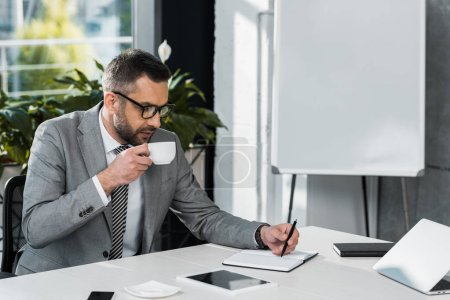 Photo for Focused businessman in eyeglasses drinking coffee and writing in notebook at workplace - Royalty Free Image