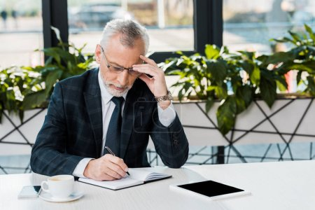 Photo for Focused mature businessman sitting at workplace and writing in notebook - Royalty Free Image