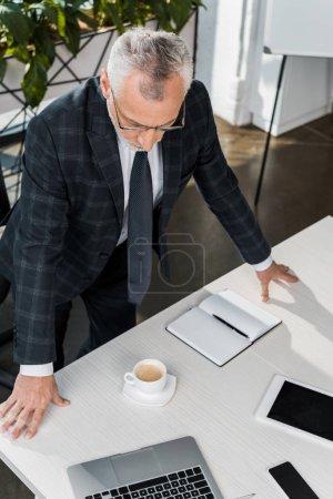 Foto de Vista de ángulo alto de buisnessman madura de gafas y traje que se inclina en la mesa de oficina - Imagen libre de derechos