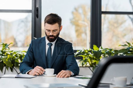 Photo for Serious bearded businessman in suit and eyeglasses holding cup of coffee while sitting at workplace - Royalty Free Image