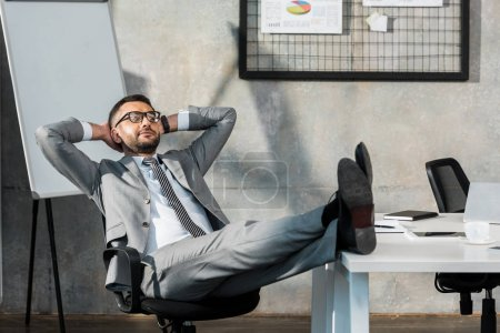 relaxed buisnessman in eyeglasses sitting with legs on table and hands behind head in office