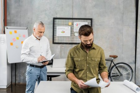 bearded businessman holding papers and mature colleague writing in notebook in office