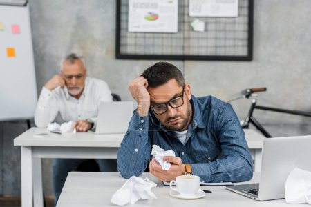 Foto de Buisnessman aburrido en las lentes que arrugado papel mientras está sentado en el lugar de trabajo - Imagen libre de derechos