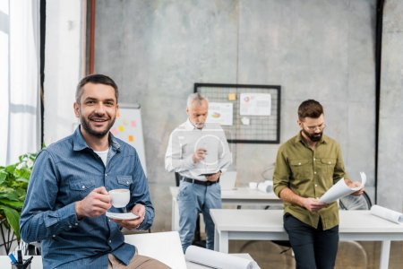handsome businessman with cup of coffee smiling at camera while colleagues woking behind