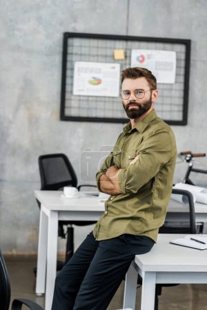 handsome bearded businessman in eyeglasses sitting with crossed arms and looking at camera in office