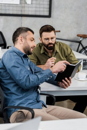 businessmen looking at notebook and discussing project in office
