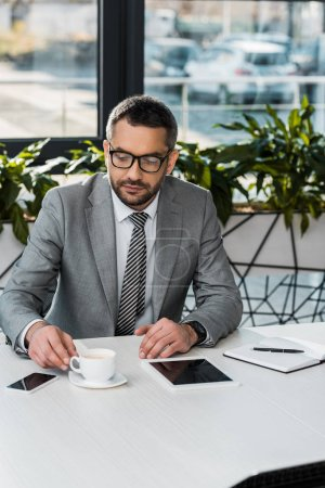 Photo for Serious businessman in suit and eyeglasses sitting at workplace and looking at cup of coffee - Royalty Free Image
