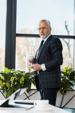 confident mature businessman holding cup of coffee and looking at camera in office