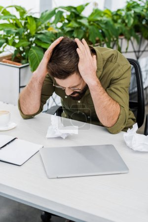 sad bearded businessman touching head and sitting at table with crumpled paper in office