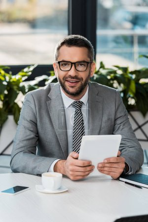 Photo for Cheerful handsome businessman holding tablet and looking at camera in office - Royalty Free Image