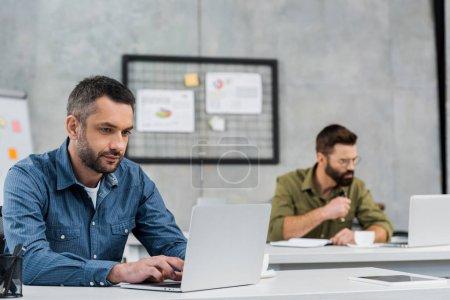 Photo pour Deux hommes d'affaires beau travailler chez ordinateurs portables au bureau - image libre de droit