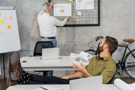 businessman sitting with legs on table and gesturing to colleague in office