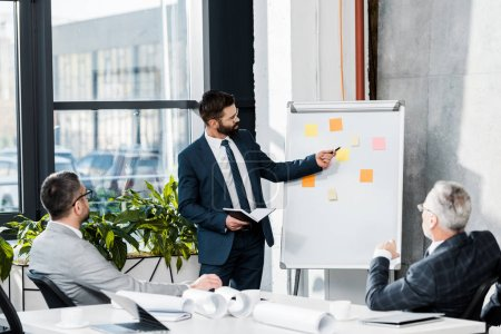 handsome businessman pointing on flipchart during meeting in office