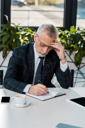 pensive handsome middle aged businessman in suit writing something to notebook in office
